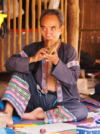historical clothing: Chiang Mai, Thailand - March 07, 2011 : Portrait of 60 year old Thai man, performing on a typical musical instrument