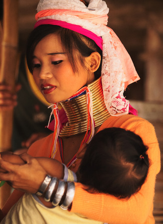 historical clothing: Chian Mai, Thailand - March 07, 2011 : Street portrait of a young long-neck woman holding a baby. There are 25 copper rings on her neck weighting 9 kilograms. She has the burden to wear them for life.