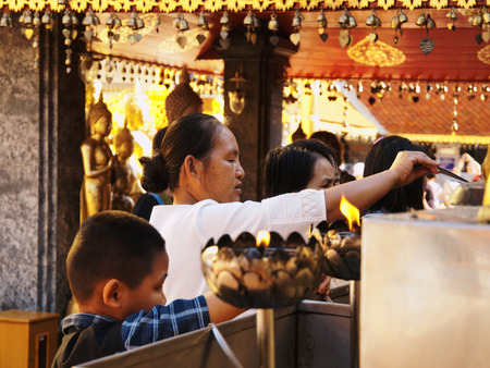Chiang Mai, Thailand - March 08, 2011 : Thai people litting lotus flower candles in Wat Phra That Doi Suthep