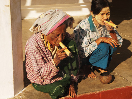 senior smoking: Bagan, Myanmar - February 25, 2011 : Senior Burmese women smoking handmade cigar inside Shwezigon Pagoda in Bagan