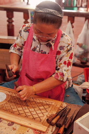 saduak: Damnoen Saduak, Thailand - March 21, 2011 : Senior woman carving wood souvenirs in Damnoen Saduak Floating Market
