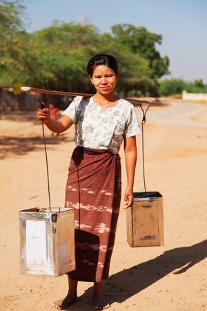 lack of water: Bagan, Myanmar - February 26, 2011 - Young burmese woman transporting water from nearby pond. The lack of fresh water is serious issue for many burmese tribes.