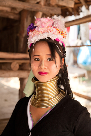 historical clothing: Chian Mai, Thailand - March 07, 2011 - Street portrait of a young long-neck woman. There are 25 copper rings on her neck weighting 9 kilograms. She has the burden to wear them for life.