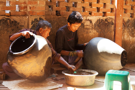lacquerware: Bagan, Myanmar - February 25, 2011 : Two young Burmese men working on lacquerware souvenirs such as plates, dishes, jewelry boxes and even furniture.