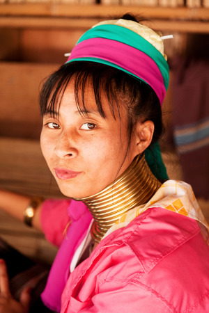 historical clothing: Chian Mai, Thailand - March 07, 2011 : Street portrait of a young long-neck woman. There are 25 copper rings on her neck weighting 9 kilograms. She has the burden to wear them for life. Editorial