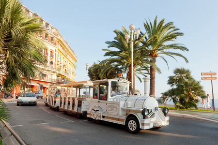 trackless: Nice, France - July 01, 2011 : Nice street live at sunset - white fun trackless train for sightseeing in front, one car at the background and pedestrians walking on Promende des Anglais