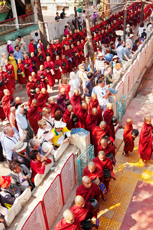 Mandalay, Myanmar - February 27, 2011 : Monks from Mahagandayone monastery gathering for their morning meal. All of them carry special buckets in which they collect food prepared from the local people. A lot of tourists are watching them as they go slowly