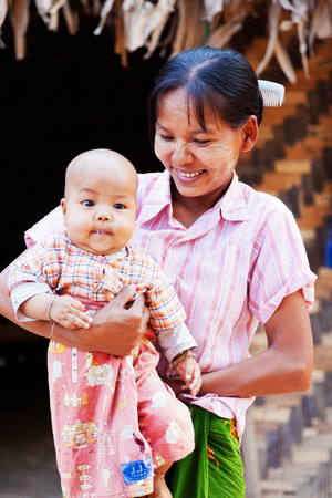 bamboo house: Mandalay, Myanmar - February 28, 2011 : Young Burmese woman with her baby in front of their bamboo house in a small village near Mandalay Editorial