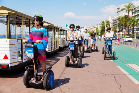 trackless: Nice, France - July 03, 2011 : Group of people riding segways on Promende des Anglais, an entertainment trackless train at left side is seen