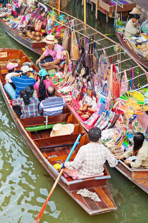 saduak: Damnoen Saduak, Thailand - March 21, 2011 : Tourists on a boat in Damnoen Saduak Floating Market looking at a variety of souveniers to buy
