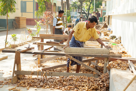local 27: Mandalay, Myanmar - February 27, 2011: Middle aged carpenters building dining tables for the largest monastery of Myanmar. Monasteries in Myanmar are run only by voluntary work from the local people. Editorial