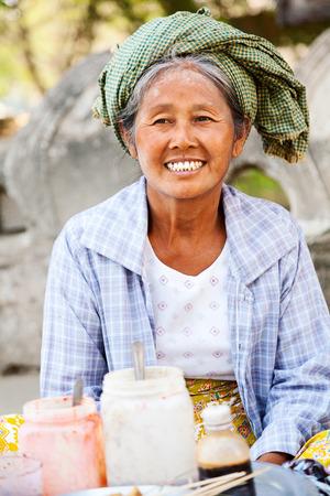 sitting on the ground: Mingun, Myanmar - February 28, 2011 : Burmese old women selling fried chicken skewers to the tourists sitting on the ground