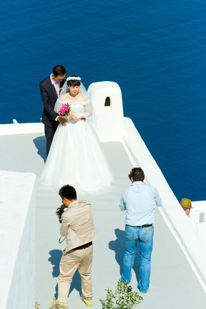 firostefani: Firostefani, Greece - May 05, 2012 : Young asian just married couple on a photo session early in the morning before the tourist are on the streets.