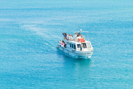 excursions: Fira, Greece - May 04, 2012 : Small cruise ship for local excursions to Nea Kameni full with tourists