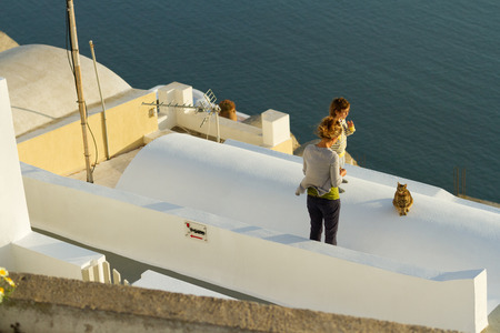 firostefani: Firostefani, Greece - May 04, 2012 : Mother and child with a cat on a roof of a summer vila at sunset Editorial