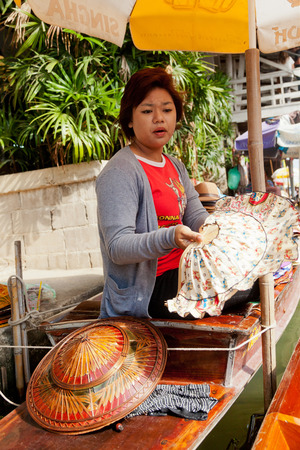 saduak: Damnoen Saduak, Thailand - March 21, 2011 : Young Thai woman selling hats in Damnoen Saduak Floating Market