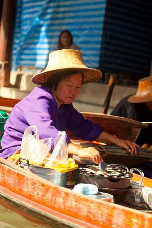 damnoen saduak: Damnoen Saduak, Thailand - March 21, 2011 : Senipr Thai woman selling freshly cooked food and fruits on a boat in Damnoen Saduak Floating Market
