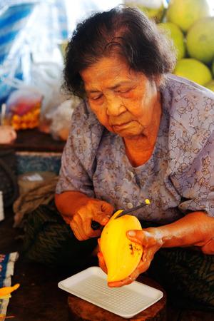 damnoen saduak: Damnoen Saduak, Thailand - March 21, 2011 : Senior Thai woman peeling mango fruit and selling fresh juices on a boat in Damnoen Saduak Floating Market