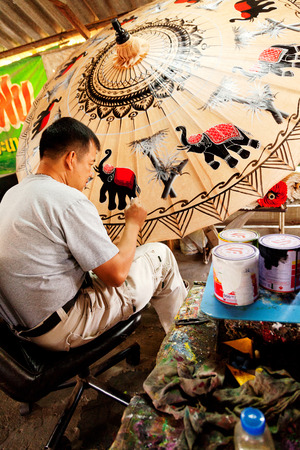 Chiang Mai, Thailand - March 06, 2011: Middle aged artist painting a big umbrella at a workshop in Chiang Mai Editorial