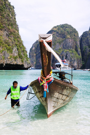 phi: Koh Phi Phi, Thailand - March 15, 2011 - Young Thai man pulling his long-tail boat to the sand on Koh Phi Phi island