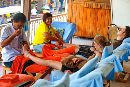 damnoen saduak: Damnoen Saduak, Thailand - March 21, 2011 : Young caucasian couple having foot massage in Damnoen Saduak Floating Market Editorial