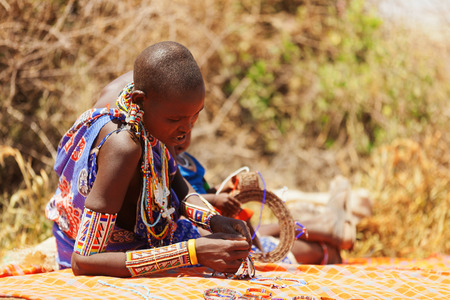 amboseli: Amboseli, Kenya - February 07, 2012 : Portrait of a young masai woman in typical clothing with handmade jewelry selling jewelry to visitors in masai village in Amboseli national park