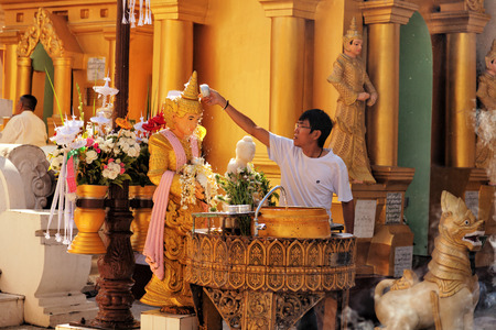 worshipping: Yangon, Myanmar - February 24, 2011 : Young Burmese man worshipping Buddha in Shwedagon Pagoda at midday