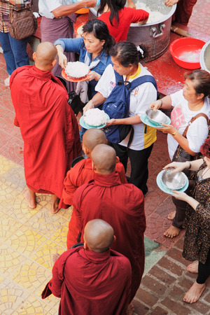 they are watching: Mandalay, Myanmar - February 27, 2011 : Monks from Mahagandayone monastery gathering for their morning meal. All of them carry special buckets in which they collect food prepared from the local people. A lot of tourists are watching them as they go slowly