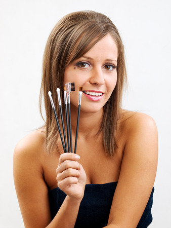 hand brushed: Close up of young woman face, holding all types of brushed in one hand Stock Photo