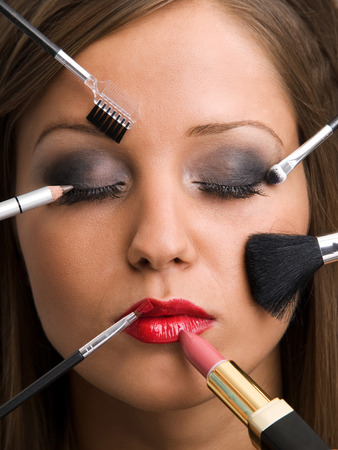 Close up of young woman face with all kinds of make up tools - brush, lipstick etc.