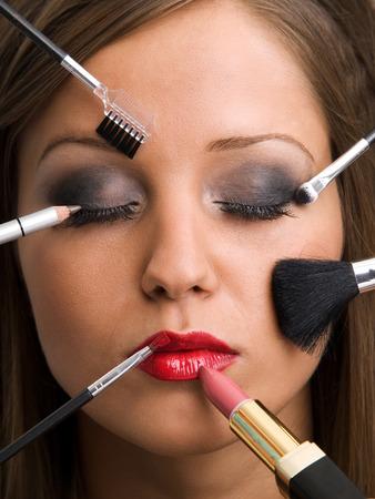 Zavřete mladá žena tvář se všemi druhy tvoří nástroje - štětec, rtěnka atd Reklamní fotografie