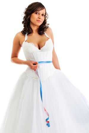 metro de medir: Novia joven con cinta alrededor de su cintura aislado en fondo blanco