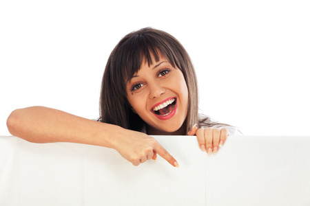 Young woman pointing behind white billboard isolated on white background Standard-Bild