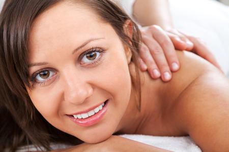 naked young woman: Young woman having a classical massage lying on white bed Stock Photo