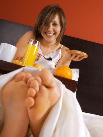 heaving: Woman in bed heaving breakfast Stock Photo