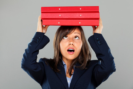 Businesswoman holding folders over her head isolated on gray background expressing emotion photo