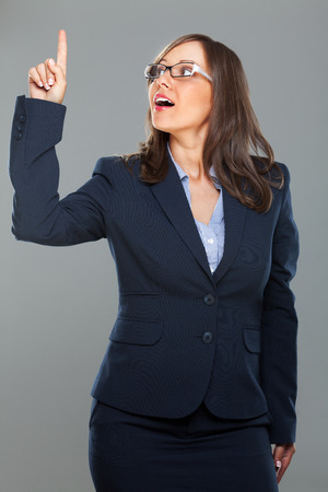 expressing: Businesswoman expressing having an idea isolated on gray background smiling Stock Photo