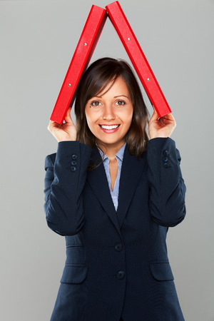 overworking: Businesswoman holding folders isolated on gray background expressing emotion