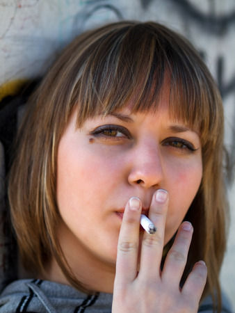 18 year old: Young student smoking in front of her school
