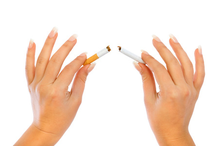 habbit: Young woman breaking a cigarette - close up of her hands