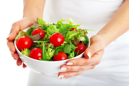 eating up: Salad bowl in woman hands isolated on white background