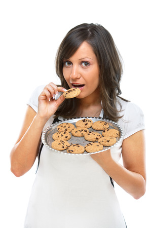 finger licking: Young woman holding a tray with homemade chocolate cookies, isolated on white