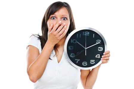 eagerness: Young woman posing at camera with clock in her hands
