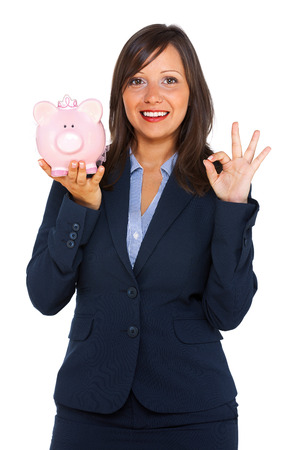 moneybox: Businesswoman holding pink pig money-box - Piggy Bank Stock Photo