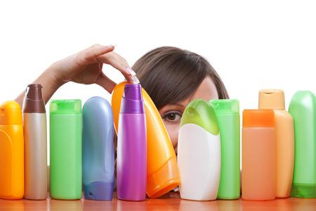 Junge Frau versucht zu entscheiden, welche Shampoo zu kaufen, isoliert auf weißem Hintergrund