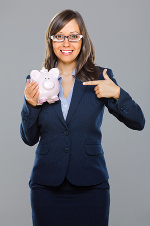 moneybox: Businesswoman holding pink pig money-box isolated on gray background smiling Stock Photo