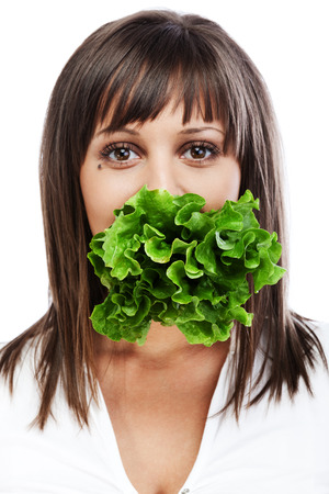 Young woman eating fresh salad isolated on white