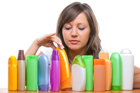 Young woman trying to choose which shampoo to buy, isolated on white background
