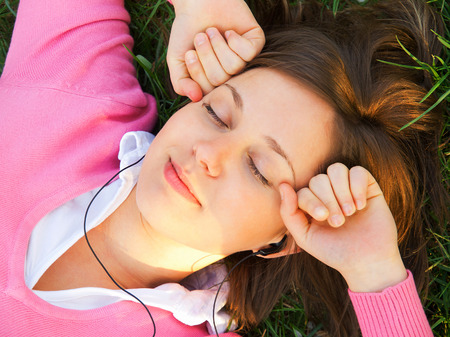 Woman listening to music on the grass Stock Photo