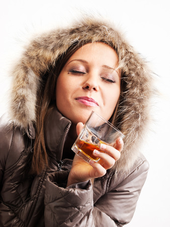 cowl: Young woman dressed in winter jacket drinking whiskey